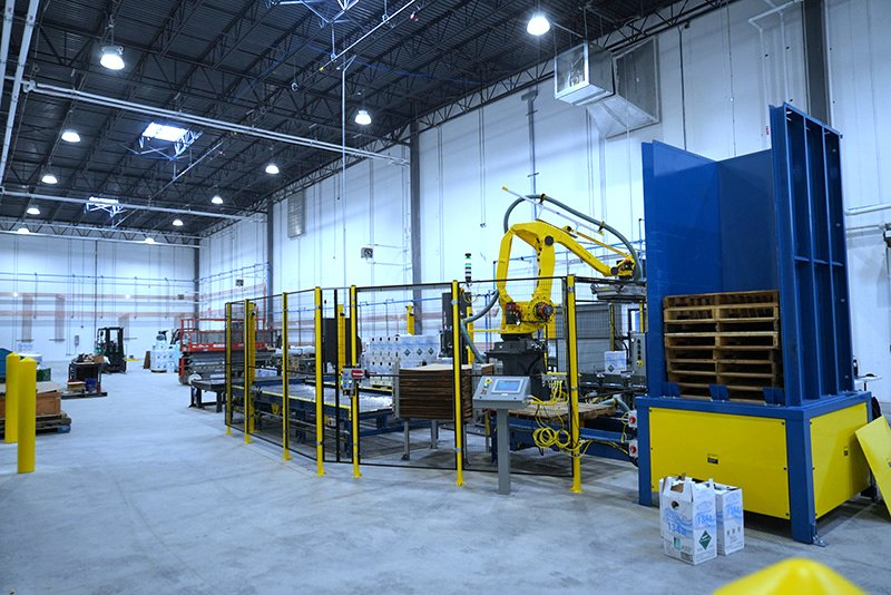 Alba pallet dispenser, Alba CDLR pallet conveyor and Alba 3 strand chain transfer conveyor used to send palletized load from Fanuc M410iB/140H carton palletizing robot to Wulftec WCA Smart stretch wrapper.