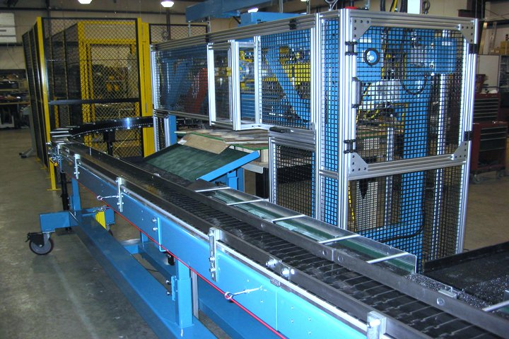 Model 366 Magnetic Furnace Unloader front view. Note: Optional part and sinter plate handling conveyors are shown. The sinter plates travel down vibratory brushed conveyors where they are returned to the front of the sinter furnace and the parts travel down steel tabletop chain conveyors where they are further processed.