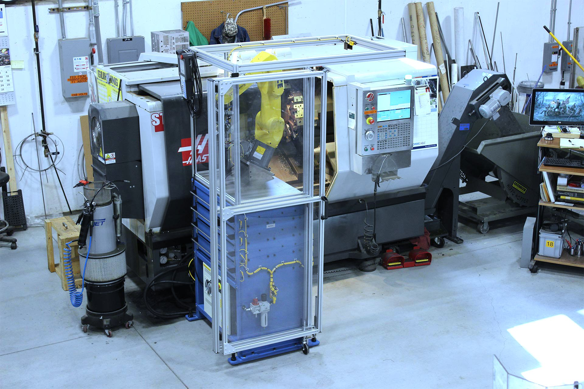 Front left side view of the Model MD MateTM Machine Tender positioned at a CNC lathe. Note: The MD MateTM is shown with all drawers closed and the bi-fold safety guard shown in the open position, illustrating how little floor space the MD MateTM uses.