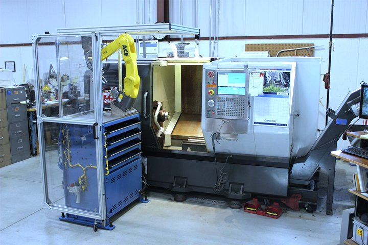 Front view of the Model MD Mate Machine Tender positioned at a CNC lathe. Note: With the robot in its home/maintenance position and the bi-fold safety guard folded back against the MD MiniDrawerTM cabinet, clear access is provided to the CNC for tooling setup or changeover.