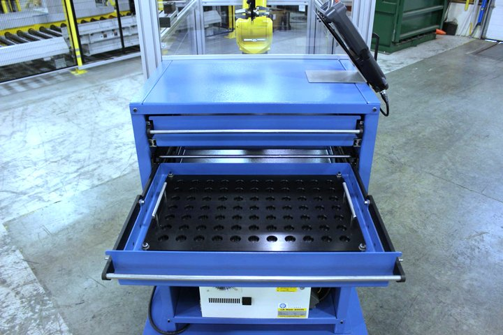 Front view of the Model MD MiniDrawer ™ Cabinet from the operator side. One of the drawers is open and includes a removable Delrin plastic fixture for customer parts. A FANUC LRMate 200iD/7L robot Teach Pendant is shown placed into a storage bracket on the top of the cabinet. The top of the cabinet may also be used for inspection processes or other operator functions as required.