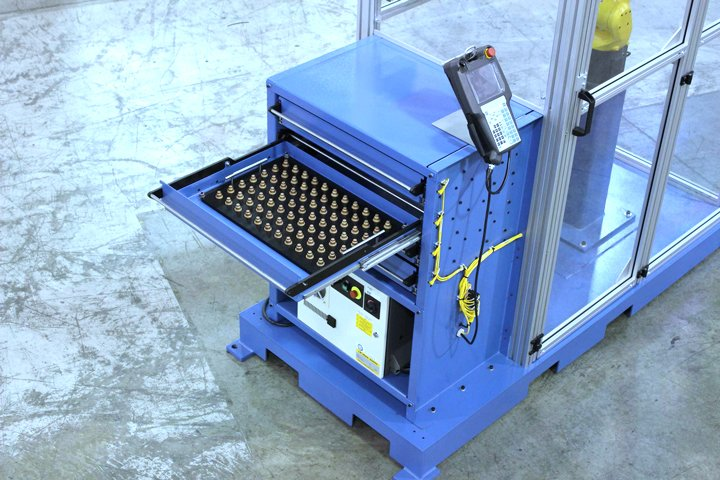 Model MD MiniDrawer ™ Cabinet with an integrated FANUC robot and the LR Mate controller shown mounted on the lower shelf. Customer parts are also shown within the Delrin plastic fixture plate in the opened drawer.