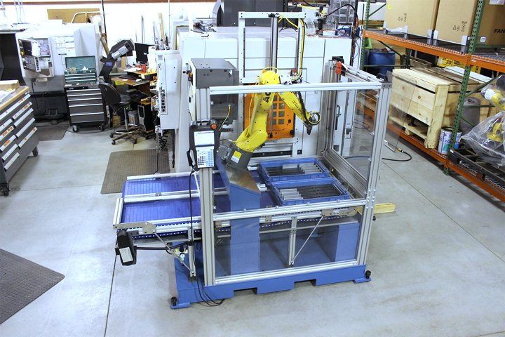 Side view of the Model RMT positioned against a CNC vertical machining center. Note: The infeed and exit conveyors extend out from the RMT providing easy access for loading and unloading parts from totes or parts directly to and from the included belt conveyors.