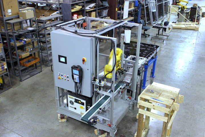 Model 220 Sizing Press Loader with vibratory infeed table for bulk loading of parts to be sized and a discharge conveyor used to transport sized parts to the next operation.