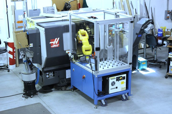 RoboCart with a fixture plate part presentation setup and a FANUC LRMate 200iD/7L robot with a dual end of arm tool integrated to a CNC lathe. The fixture plate setup allows the operator to load a quantity of parts on the fixture plate for processing. The robot will unload the parts individually from the fixture plate, process them within the lathe and then reload the fixture plate with the completed part. Once all parts have been processed, the robot will signal the operator for reloading.