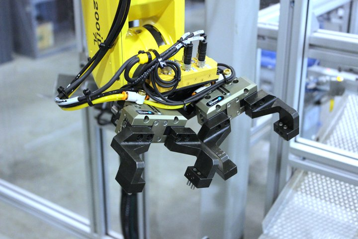 Typical dual end of arm tool for the Model 220 Sizing Press Loader. Note the angled gripper mounting design, which provides needed tooling clearance during the sizing press robotic load/unload operation.