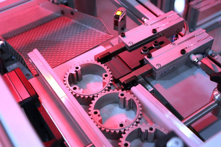 Typical part escapement on the Model 220 Sizing Press Loader. Note the discharge chute shown is flowing toward a servo turntable, where FANUC iRVision is used to orient the part prior to sizing press load.