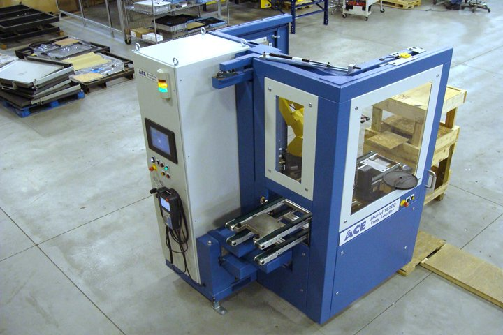 Top front isometric view of the TL200 Tray Loader and its compact footprint. The tray conveyors are extended to enable easy operator access. Notice the sample disc shown in the access door lower window frame. The sample disc provides an easy way to receive sample parts from the mold press. A sample request is initiated at the graphical user interface. The FANUC 6-axis robot will place the very next part onto the sample disc. The operator simply rotates the disc 180 degrees to retrieve the sample part.
