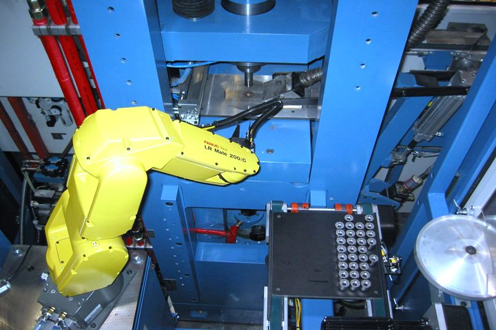 Model TL200 Tray Loader FANUC 6-axis robot picking a part from the mold press and placing it onto the sinter tray using a mechanical gripper tool. Once the tray is full it will be discharged and a new tray will be introduced. Notice the tight spacing of the parts maximizing tray density.