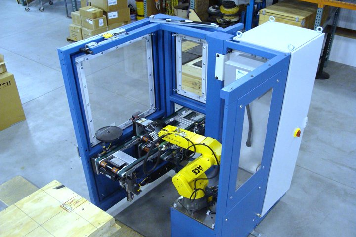 Model TL200 Tray Loader from a press point of view. The FANUC 6-axis robot is positioned off to the side to provide enhanced press access. The access door and tray conveyors are shown in closed position ready to receive parts.