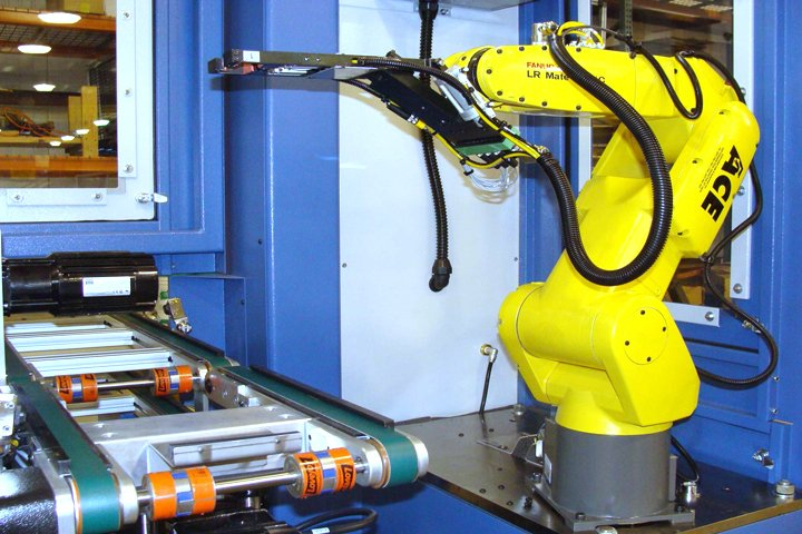 Model TL200 Tray Loader tray conveyor setup. The tray conveyor where molded parts are placed onto trays is mounted on a pneumatic lift to enable transitioning of full and empty trays to the FANUC 6-axis robot.