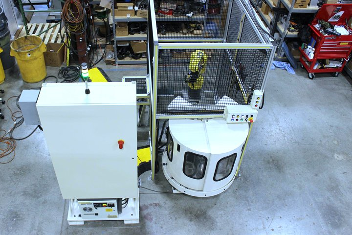 Front top view of the Model WS8100 Mate Machine Tender. Note: The main control panel with the robot controller mounted underneath is shown on the left and includes a fork truck base for ease of relocation.