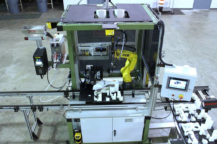Small robotic assembly cell inserting and driving screws to fasten a string trimmer shroud to the main power head assembly. The cell features a FANUC LRMate 200iD tabletop robot with laser safety scanner, programmable logic controller and touch screen for cell control and messaging.