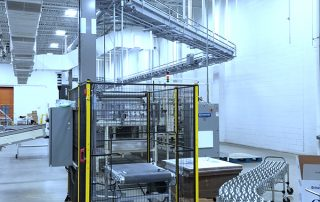 Qimarox PRORUNNER Mk 1 Vertical Conveyor feeding raised Hytrol EZ Logic 24-volt zero pressure accumulation conveyor line