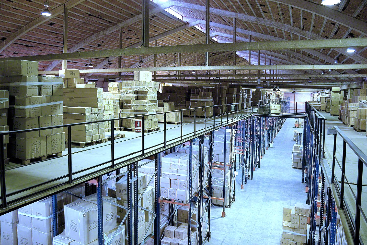 Mezzanine installation above pallet racking with catwalk connecting to mezzanine across the aisle. Palleted packages are stored in the pallet racking as well as on the raised mezzanine floor.
