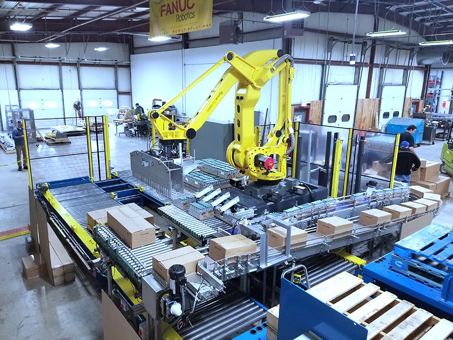 FANUC M-410 palletizing robot receiving cases from Hytrol conveyor infeed lines