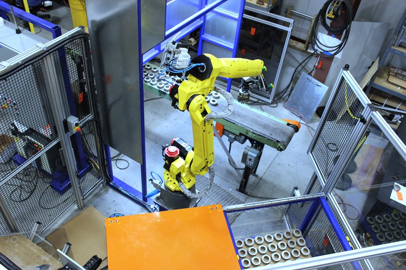 Overhead view of FANUC M-20iA robot with FANUC iRVision and line tracking, Keyence laser sensor used for Z-axis offset, Schunk quick change gripper fingers