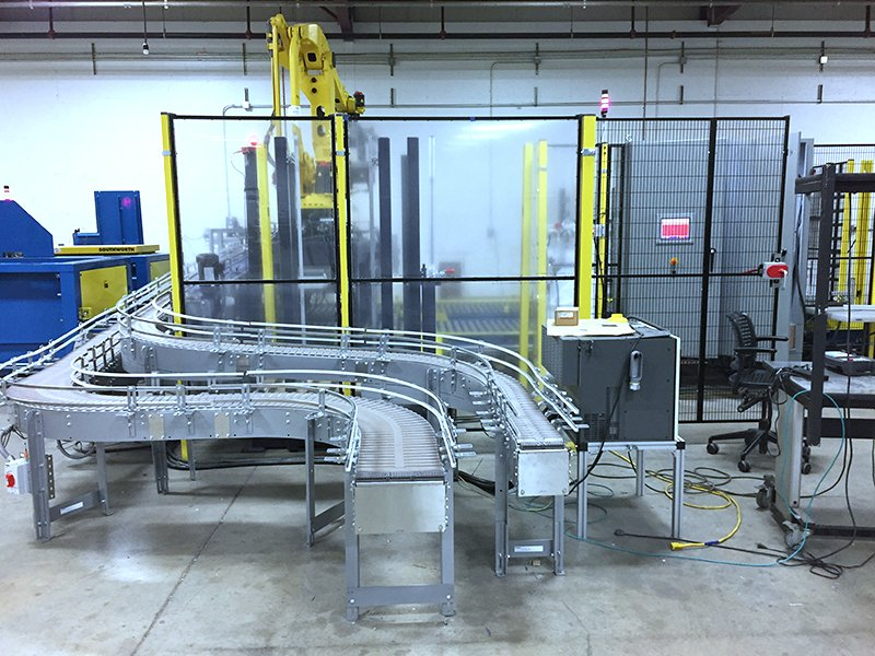 FANUC M-410iB/140H case palletizing robot behind a Troax safety fence with Hytrol 138 ACC Conveyors infeed lines and 2 Alba CDLR conveyor for pallet outfeeds