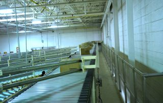 Packages being diverted to outfeed lines by Hytrol Shoe Sorter Conveyor