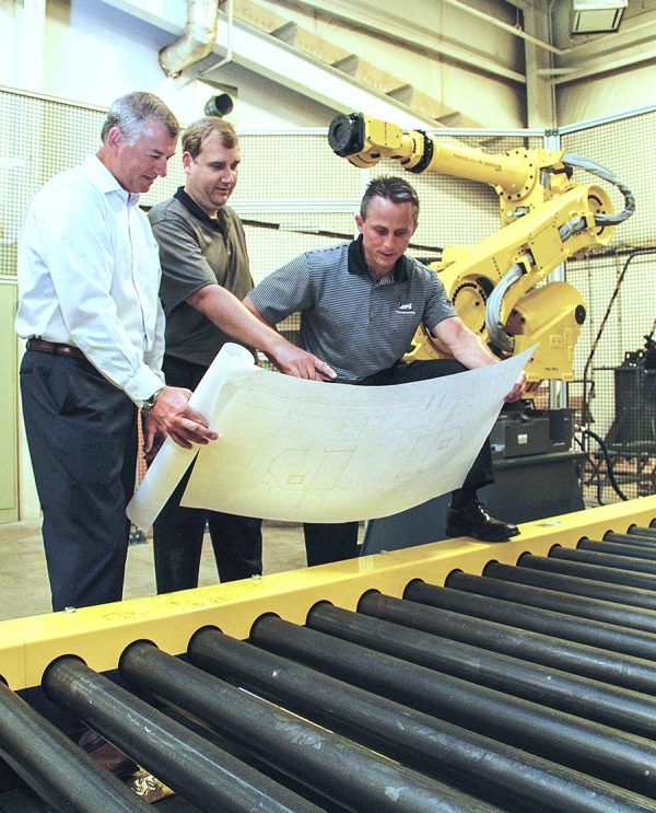 Jeff Gambrill (right) and Bob Manion (left) after their purchase of Aloi Materials Handling looking at CAD drawings with engineer Rich Mikulec over a CDLR conveyor and a FANUC robot in the background.