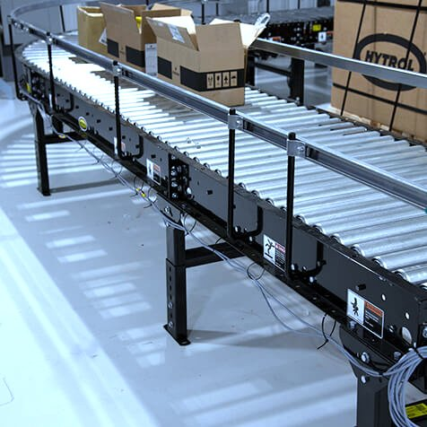 Hytrol Accumulation Minimum Pressure Conveyor with multople open cardboard boxes on the line entering a 90 degree turn