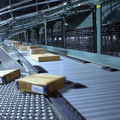 Shoe sorters diverting multiple boxes moving down the line of a Hytrol ProSort Sliding Shoe Sorter Conveyor