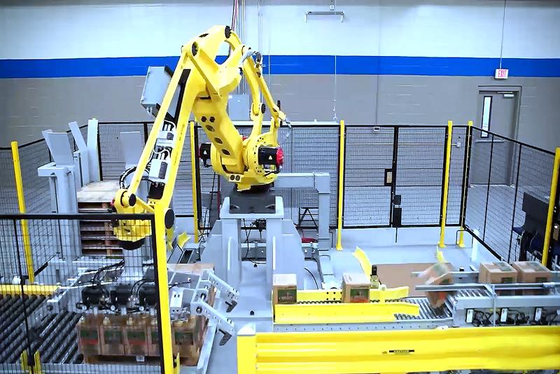 Robotic palletizer placing cases onto pallet load.