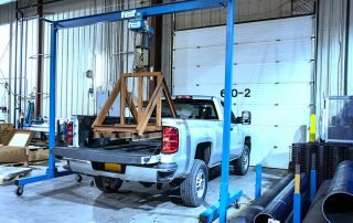 1 Ton Gorbel Gantry Crane hoisting steel work over the bed of a pick up truck in a facility