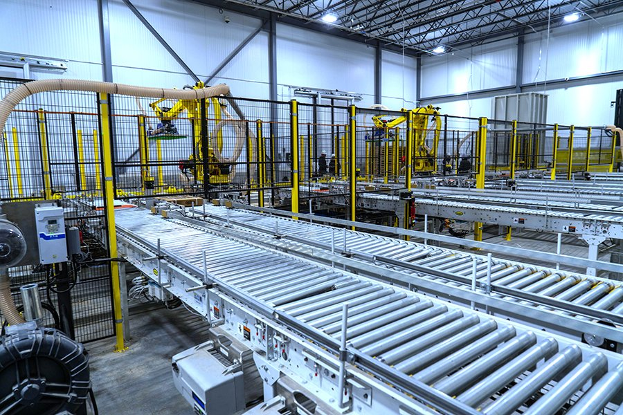 Back view of Hytrol conveyors leading into 2 Fanuc robotic palletizing cells with multiple empty pallets