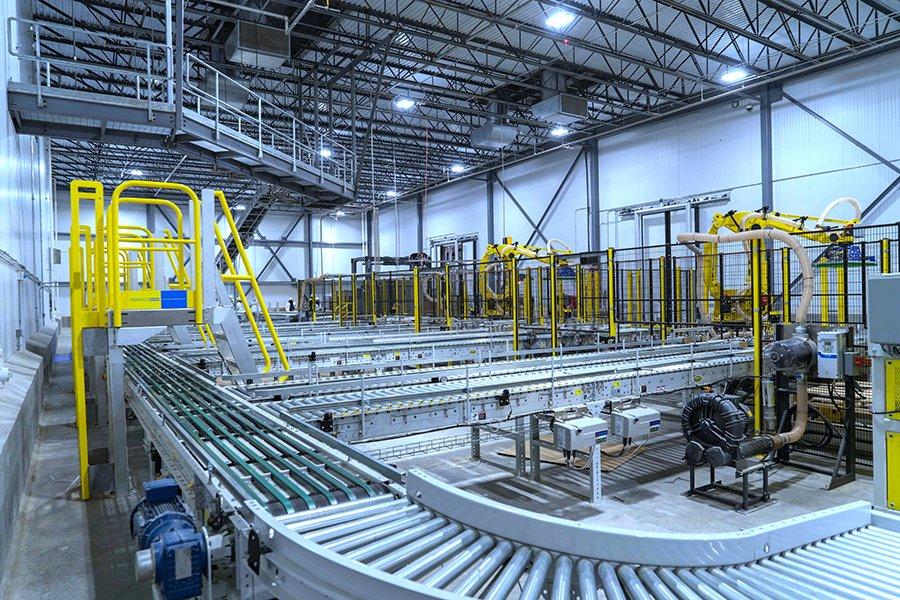 Hytrol right angle sortation conveyor leading into 2 robotic palletizing cells