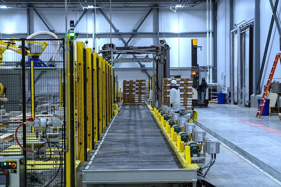 Adaptec tech inspects Alba pallet conveyor in front of a Wulftec WCRT-200 rotary arm stretch wrapper